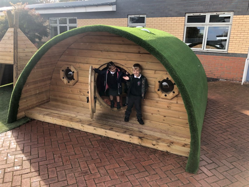 Children standing next to a playground den - the hobbit house