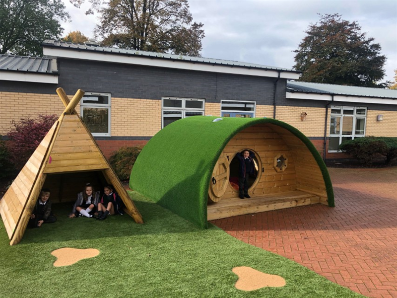 Children sitting in playground dens socialising