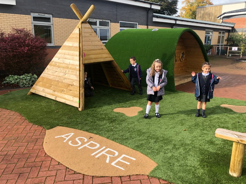 Children standing on artificial grass surfacing