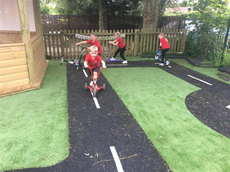 4 children riding bikes, trikes and scooters on a black saferturf roadway