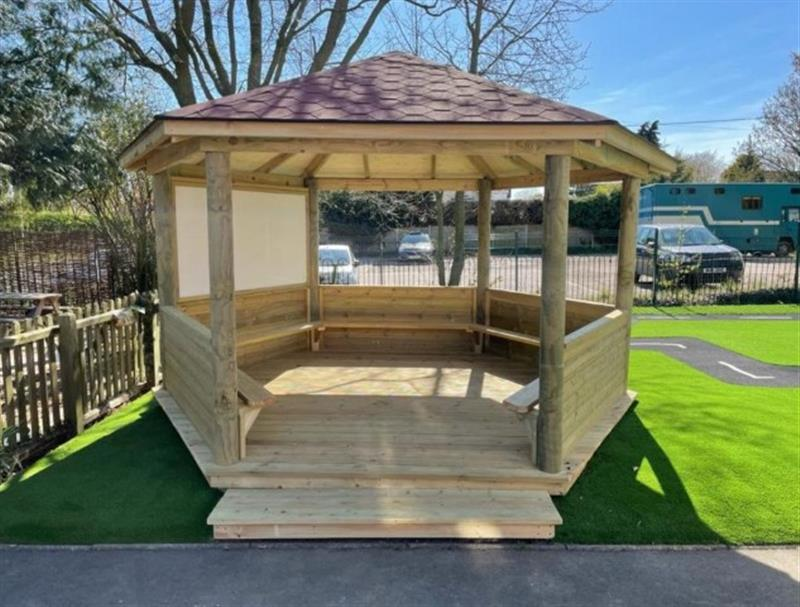 A timber gazebo with decked base and ramp installed onto artificial grass