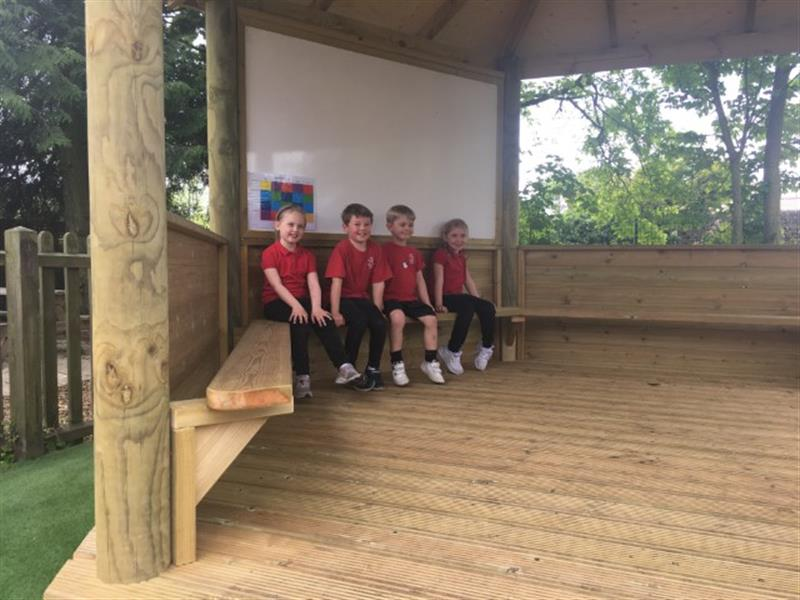 4 children sat on the internal benches in a gazebo under a giant whiteboard