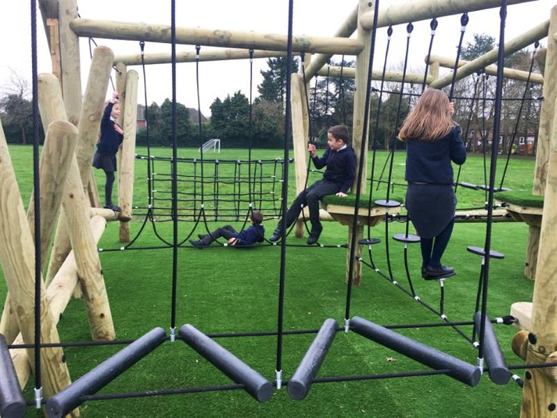 Four children in black school uniforms playing on pentagon plays grizedale forest circuit