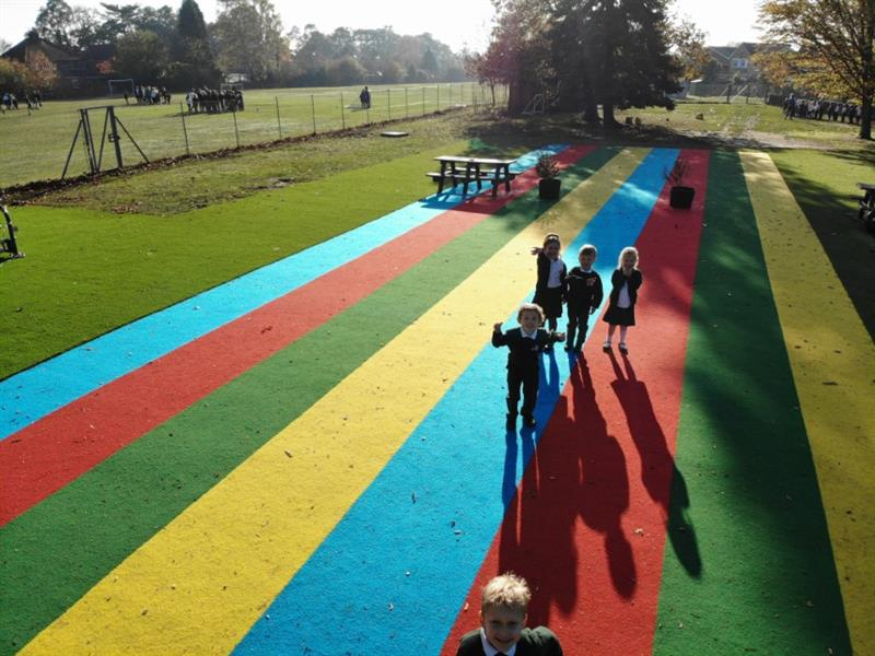 Children running down multi coloured saferturf running lanes
