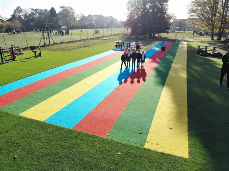 Children stood on multicoloured saferturf running lanes