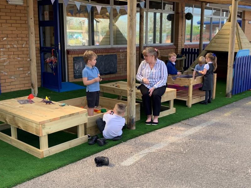 3 children playing at the construction table in front of the wigwam whist one teacher sits down talking to 2 children who are playing in the sandbox which has been installed onto artificial grass.