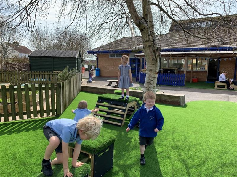 3 children playing with the get set, go! blocks, whilst one boy with a blue jumper runs on the artificial grass next to the blocks. There is a large tree behind the blocks.