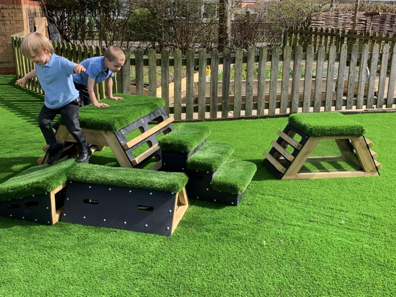 2 boys wearing light blue polo tops are playing on the get set, go! blocks that have been placed on the artificial grass in front of the timber fencing.