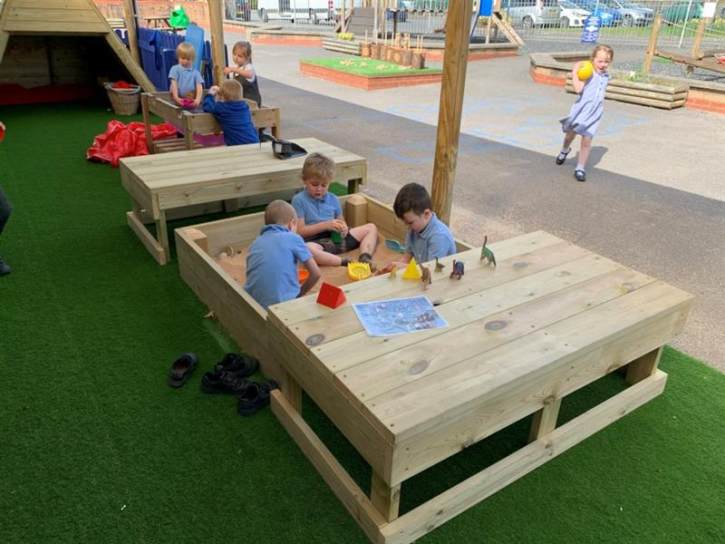 3 boys sat inside of a sandbox playing with the sand whilst 5 toy dinosaurs sit on top of the box. Behind the sandbox is the construction table where 3 more children play and one girl wearing a summer dress runs past with a yellow ball.