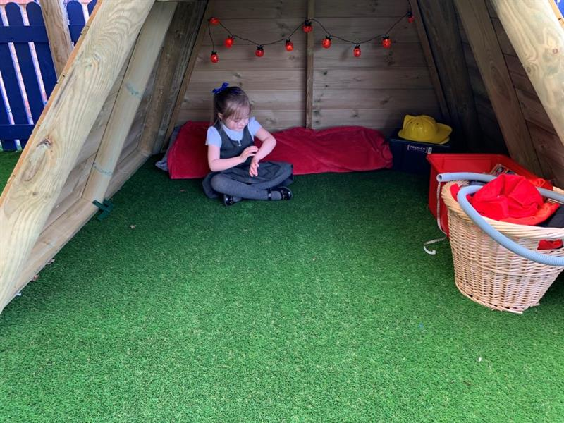 one girl wearing a school dress is sat on artificial grass inside of a wigwam den where there are ladybird fairy lights hanging down, yellow builders hats in the corner and a basket and red box.