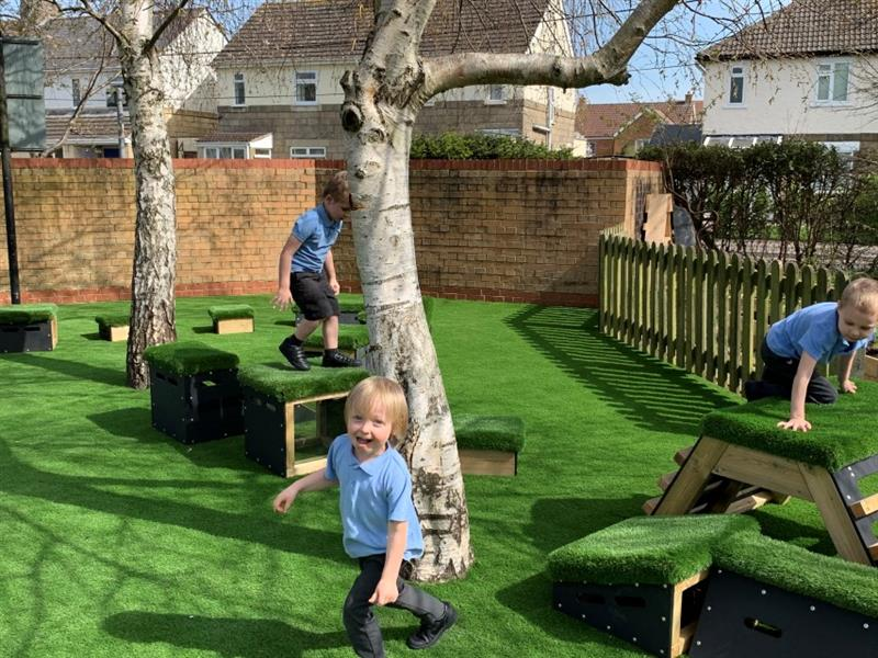 3 boys wearing light blue polo tops playing on the get set, go! blocks that have been placed on the artificial grass weaving in between two trees.