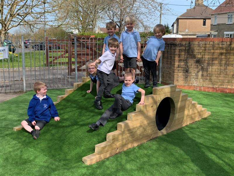 7 children, 4 wearing blue polo tops, one wearing a white polo top, one wearing a grey dress and one wearing a blue jumper, are playing on top of the climb through tunnel with a hill which is covered with artificial grass.