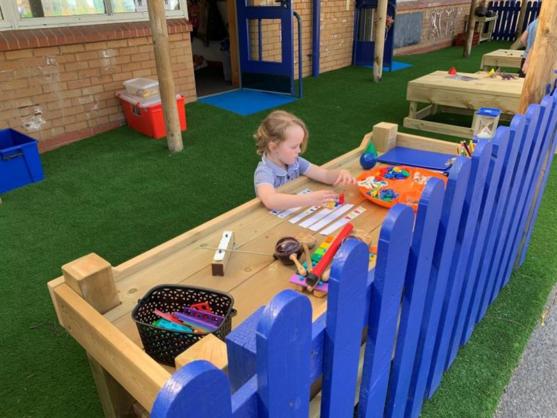 one girl wearing a school summer dress is stood at a construction table playing with small multicoloured blocks. The table has been placed behind blue fencing and on top of artificial grass.