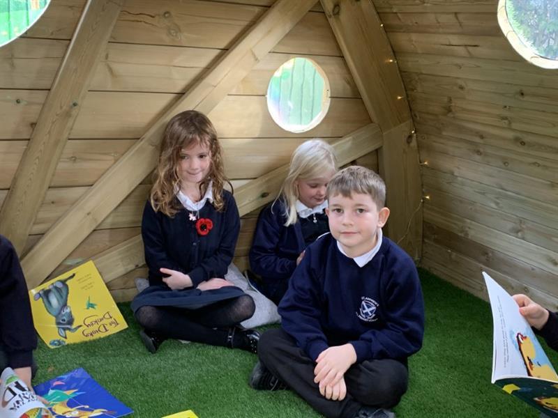 Children reading inside a playground den