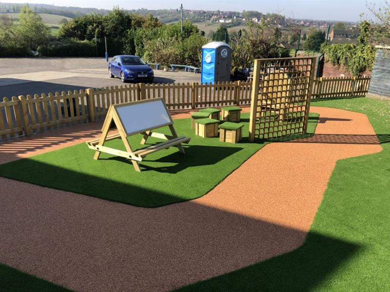 Playground seating surrounded by wet pour surfacing and artificial grass