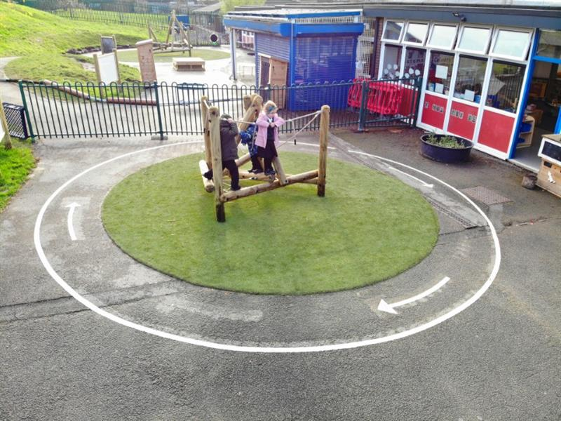 A climbing frame installed onto artificial grass surrounded by playground markings