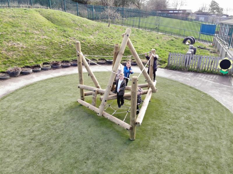 A log and rope eyfs climbing frame installed onto artificial grass