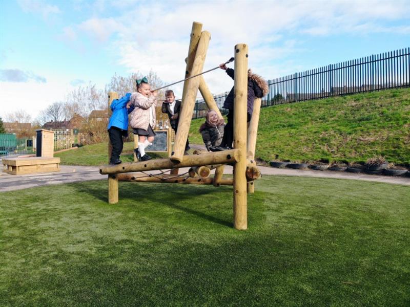 Reception children climbing on a playground climbing frame