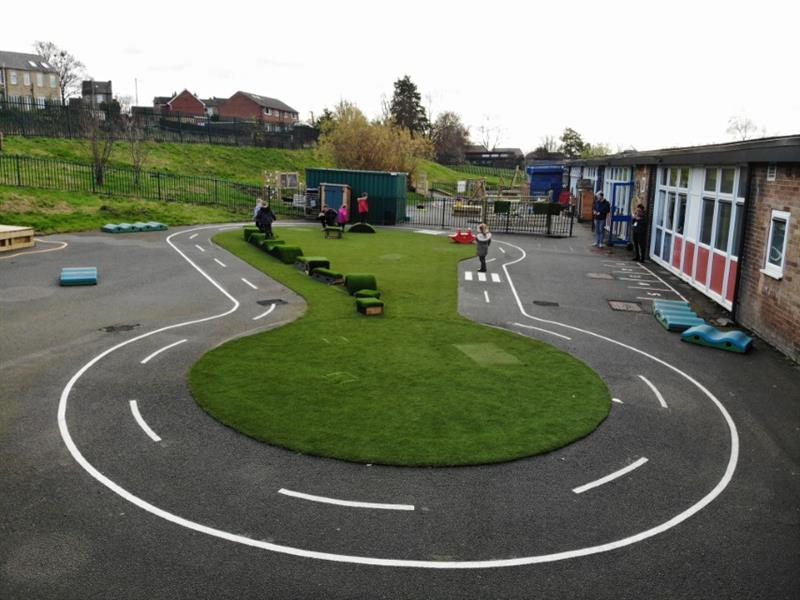 Thermoplastic playground markings installed around artificial grass surfacing
