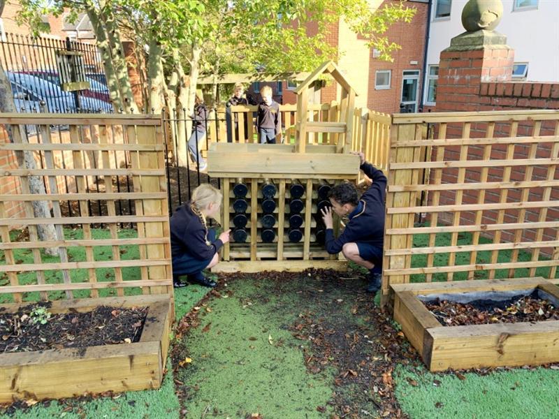 Children observing a playground bug hotel