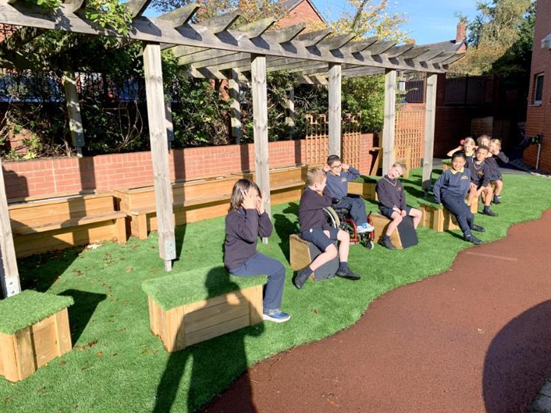 Children sitting on school playground seating