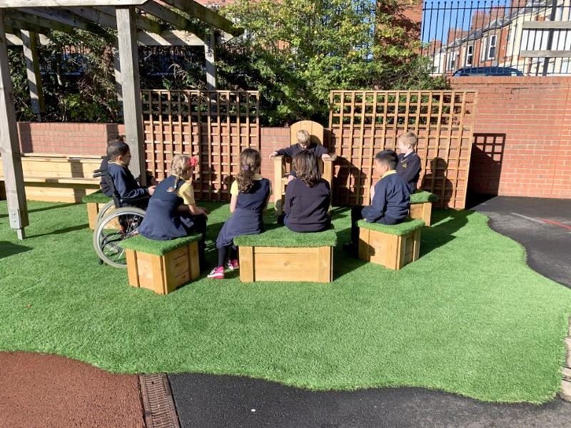 Children listening to a story sat on playground seating