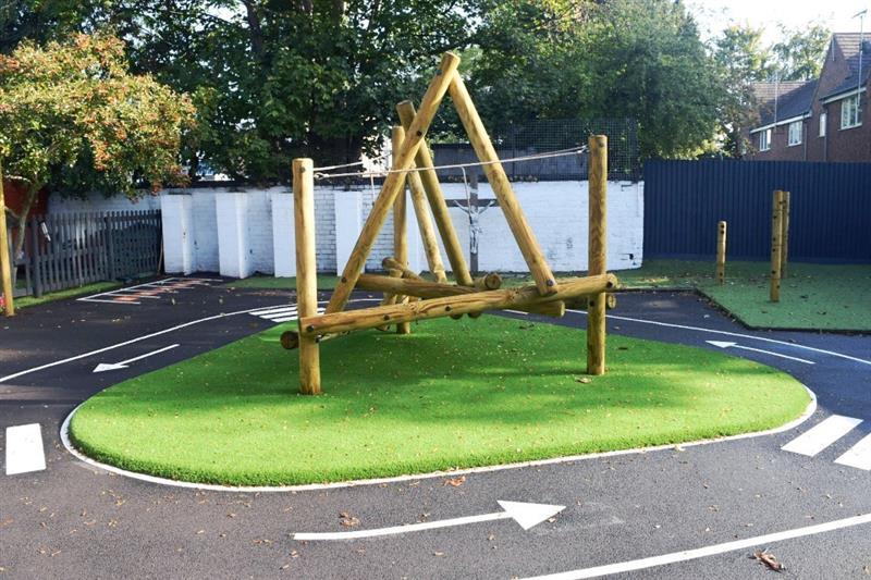 A log climbing frame installed onto artificial grass surfacing