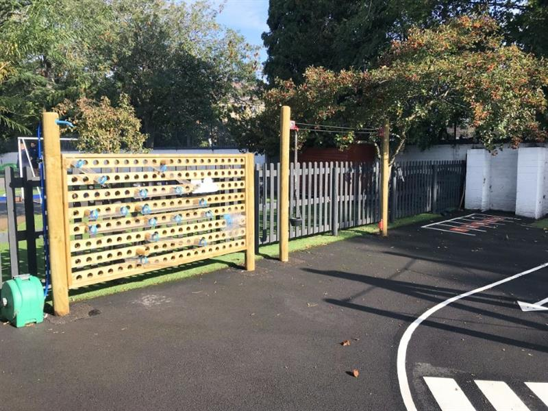 A pentagon play water wall installed onto tarmac on a school playground