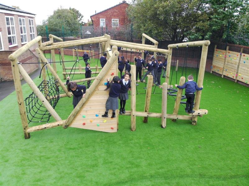 Pentagon Play's Puzzlewood Forest Circuit installed into the school playground with artificial grass underneath