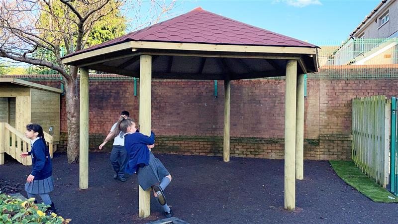 A 5m gazebo with bright red roof installed in the corner of the school playground