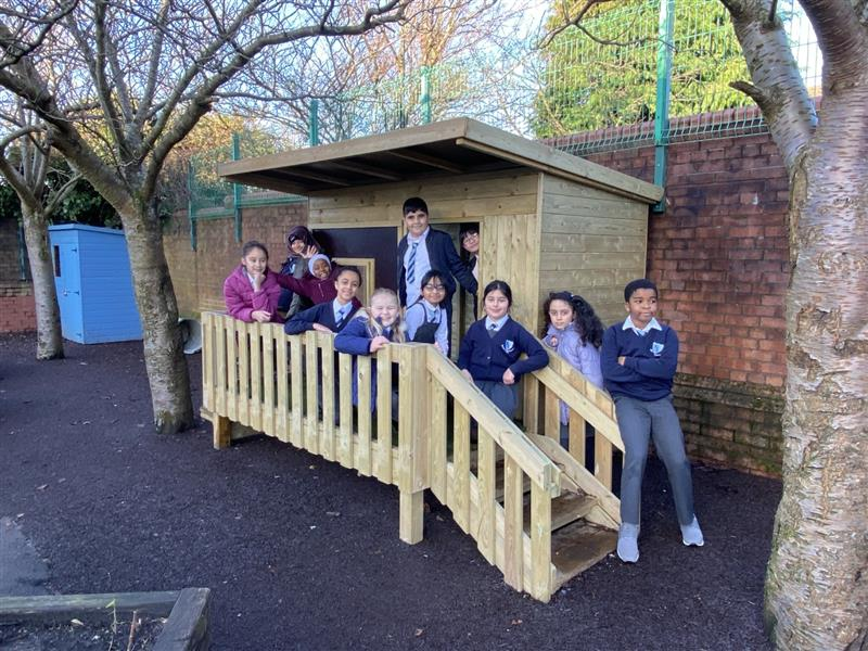 KS2 children sat in a Look Out Cabin playing role play games