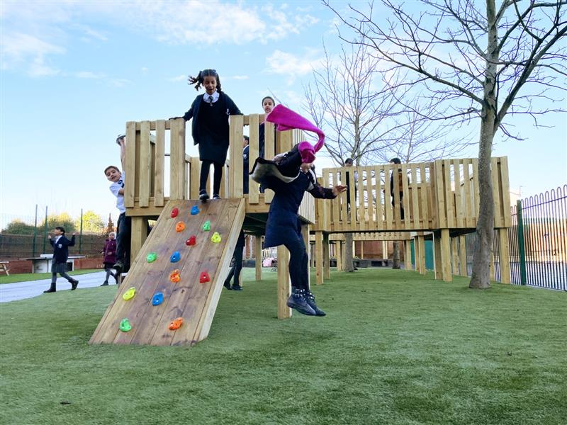 A child jumping off a school playground tower and landing on the artificial grass below