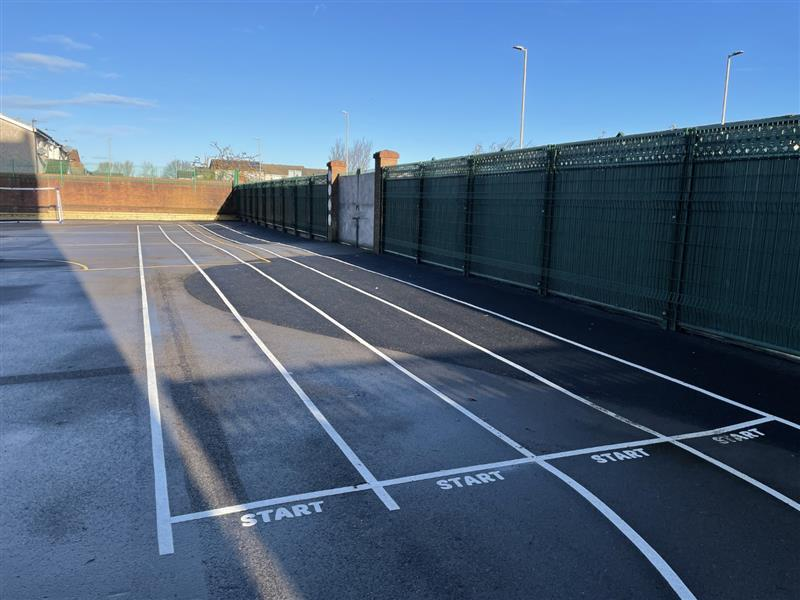 A photo of a 4 lane running track with start and finish on the school playground made out of thermoplastic playground markings