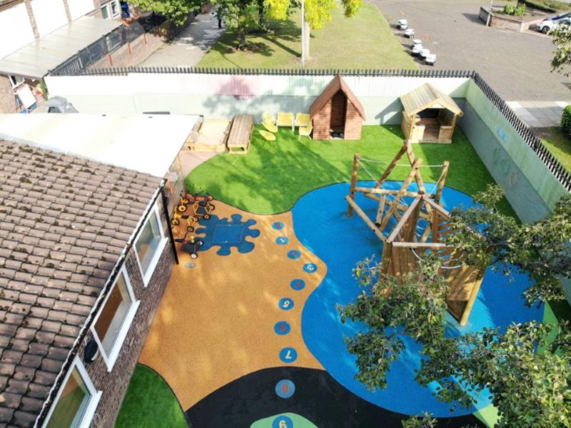 Ariel photo of an EYFS playground design with blue and orange wet pour surfacing
