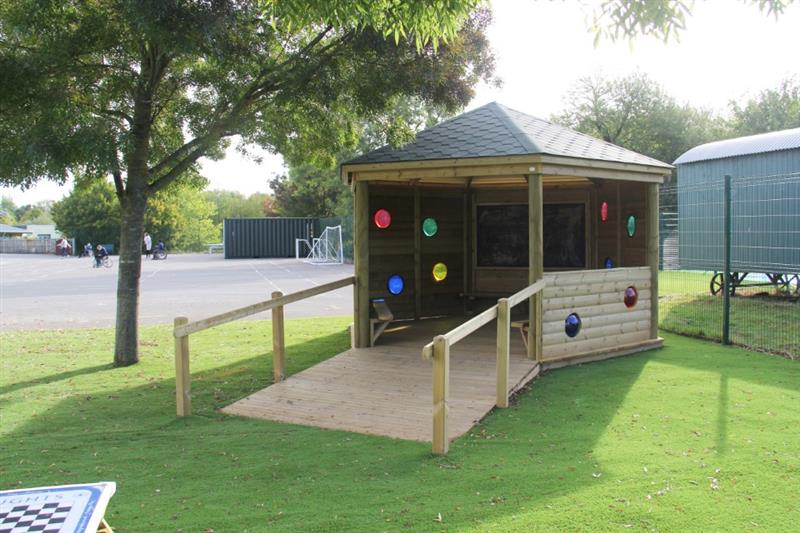 A sensory outdoor classroom with ramp and hand rail