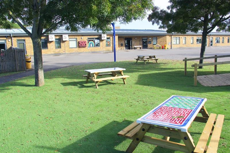 Artificial Grass with picnic benches placed on top of it in the school playground