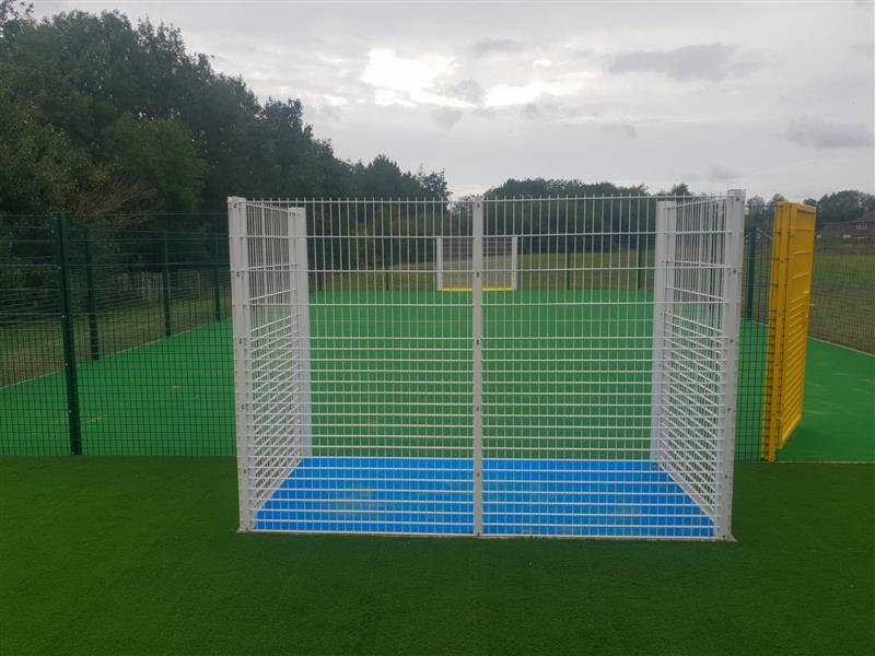 A multi use games area with bright yellow gate and white goal ends