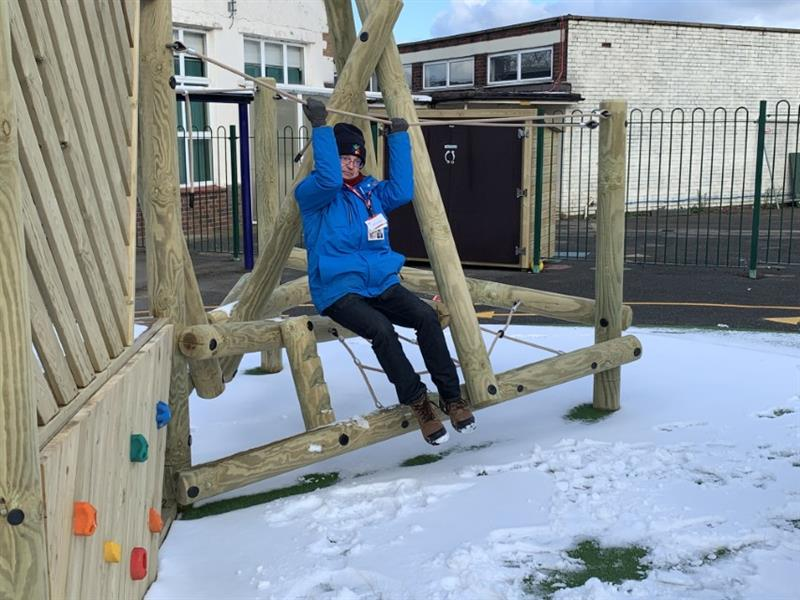 Sam Flatman from pentagon play swinging on a climbing frame