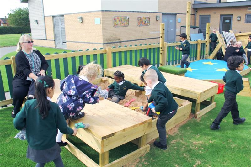 EYFS children playing in a playground sand box