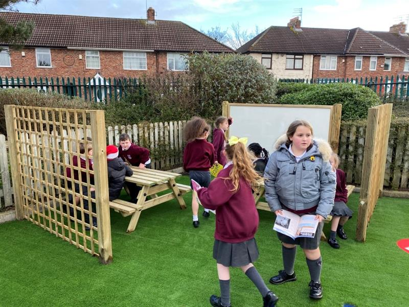 9 children in a corner area, 5 children sat on picnic benches, 2 children stood at the entrance and 2 children stood near a giant whiteboard. Installed onto artificial grass.