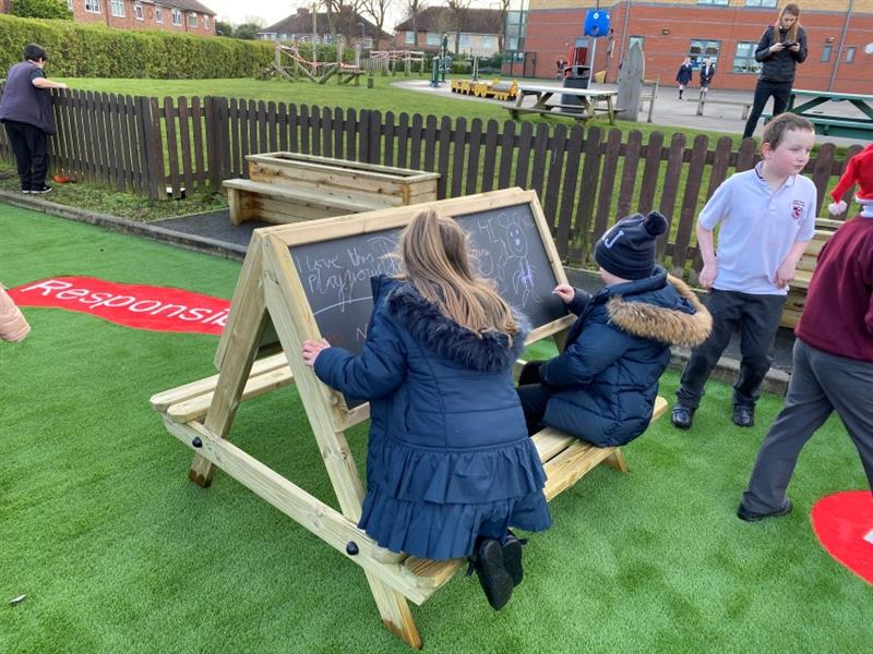 Two children, one boy and one girl sat at an easel table scribbling onto the chalkboard whilst two children play nearby.