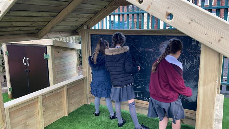 3 children, all girls, one wearing a navy blue coat and one wearing a black coat, inside a giant playhouse with chalkboards scribbling onto the chalkboard.
