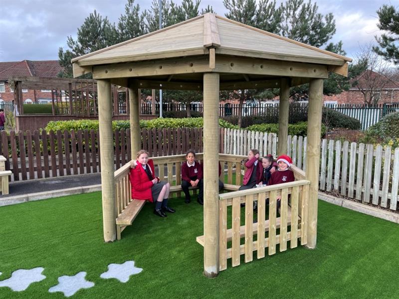 6 children wearing maroon school uniform, one child wearing a red coat and one child wearing a Father Christmas hat, sat inside a 3.5m hexagonal gazebo.