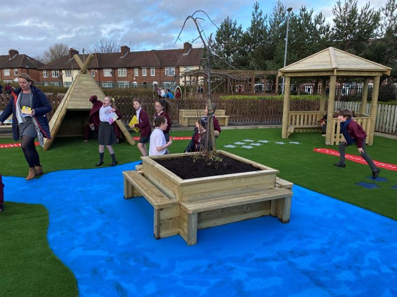 7 children and 1 teacher playing in a playground near planter benches which have been installed onto blue safeturf surrounded by artificial grass.