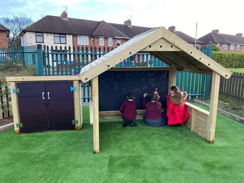 3 children, 1 boy and 2 girls inside a giant playhouse with chalkboards scribbling on the chalkboards, which has been installed onto artificial grass.