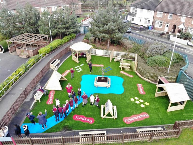 Aerial view of many children stood in the playground on blue safeturf and artificial grass observing their new outdoor space.