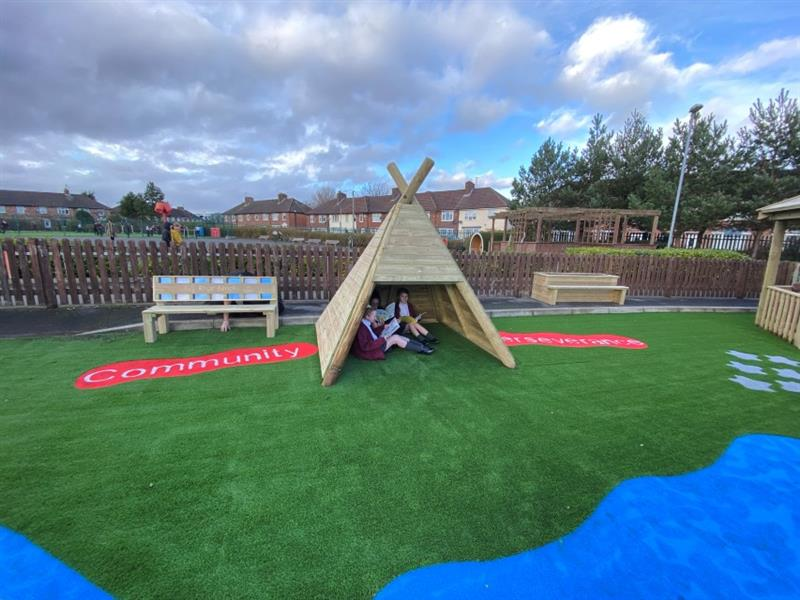 3 children sat underneath a wigwam reading, which has been installed onto artificial grass next to the bespoke memorial bench for former pupil Rhys Jones.