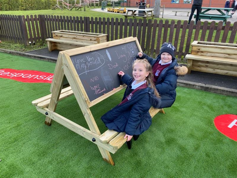 2 children smiling at the camera, one boy and one girl, sat on an easel table, scribbling onto the chalkboard which has been placed onto artificial grass.