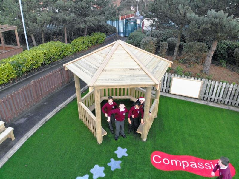 4 children underneath a 3.5 hexagonal gazebo installed onto artificial grass, one child is wearing a Father Christmas hat. One child running past the gazebo.