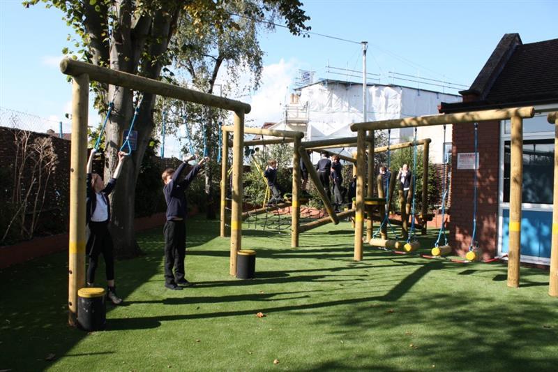 Children climbing on playground active play equipment